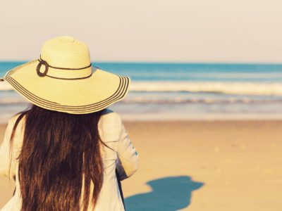 Woman in a hat sitting on the beach toward sunset