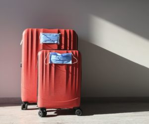 Two red luggages with protective masks to protect against coronavirus, global epidemic concept. Cancelled flights. Stop Travel.